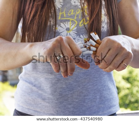 Quit Smoking, woman hands breaking bunch of cigarette.  Selective focus, motion blur - stock photo