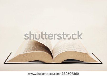quite new open book lying on the table on a light background - stock photo
