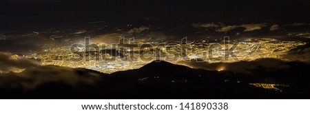 Quito, a long City at night. Was taken at the top of Pichincha active volcano. Panoramic photo of Andes from Ecuador - stock photo