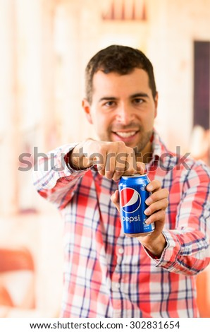 QUITO, ECUADOR - AUGUST 3, 2015: Attractive young man smiling opening a Pepsi Cola can - stock photo