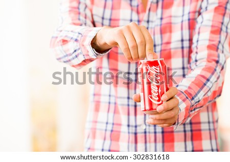 QUITO, ECUADOR - AUGUST 3, 2015: Closeup of young man hands opening a Coca-Cola can - stock photo