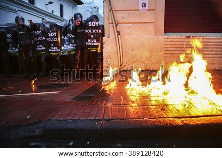 Quito, Ecuador - August 27, 2015: Sidewalk on fire during violent protests, large group of riot police awaits. - stock photo