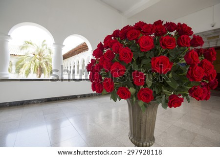 QUITO, ECUADOR, FEBRUARY 26: Huge bunch of red roses in stone vase located in the Presidential Palace, Quito. Ecuador 2015. - stock photo
