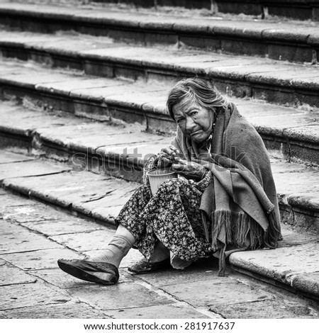 QUITO, ECUADOR - JAN 2, 2015: Unidentified Ecuadorian old lady eats on the stairs in the street. 71,9% of Ecuadorian people belong to the Mestizo ethnic group