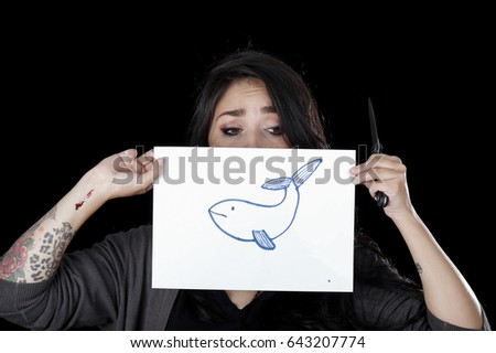 Quito, Ecuador - May 09, 2017: Anxious teenager drawing a whale over a sheet of paper, social suicide concept as a sociology metaphor for crowd or herd mentality and group decisions resulting in