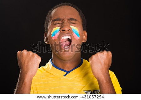 Quito, Ecuador - May 25, 2016: Headshot dark skinned male wearing yellow ecuadorian football shirt in front of black background, flag facial paint, eyes closed and mouth open cheering with arms raised