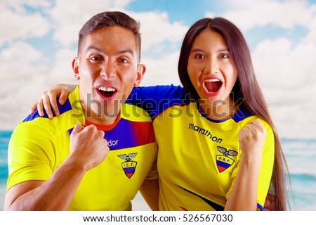 QUITO, ECUADOR -8 OCTOBER, 2016: Young ecuadorian couple wearing official Marathon football shirt standing facing camera, very engaged body language watching game with great enthusiasm, blue sky and
