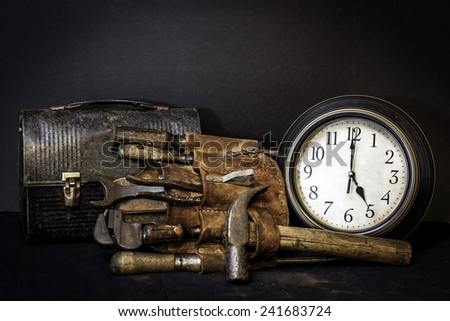 Quittin time.  Vintage tool belt and lunch box with tools and clock showing 5 o'clock.