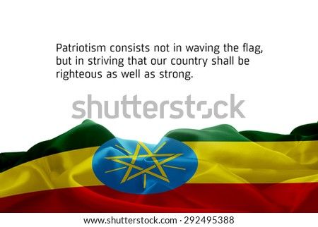 """Quote """"Patriotism consists not in waving the flag, but in striving that our country shall be righteous as well as strong"""" waving abstract fabric Ethiopia flag on white background - stock photo"""