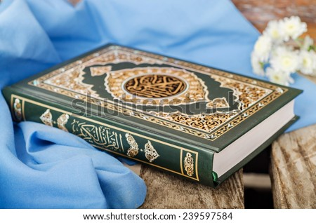Quran - holly book of islam with spring flowers and blue scarf on wooden background. Selective focus on book - stock photo