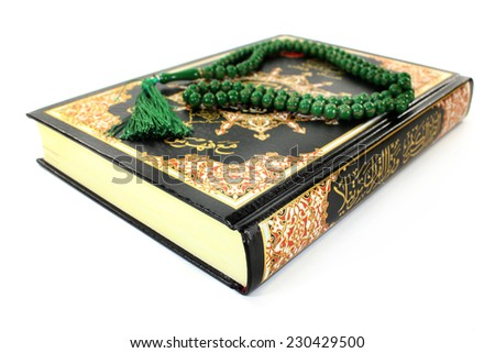 Quran with rosary in front of white background - stock photo