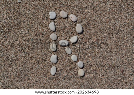 R letter made of stones on sand  - stock photo