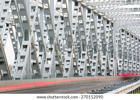 RAAMSDONKVEER, NETHERLANDS - APRIL 7: Traffic leaving light trails in the structure of the steal bridge over river Bergsche Maas in Noord-Brabant, on April 7, 2015 in Raamsdonkveer, the Netherlands - stock photo