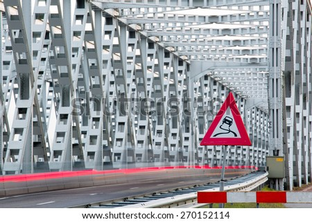 RAAMSDONKVEER, NETHERLANDS - APRIL 7: Traffic sign of the steal bridge over the river Bergsche Maas with cars leaving light trails , on April 7, 2015, in Raamsdonkveer, the Netherlands - stock photo