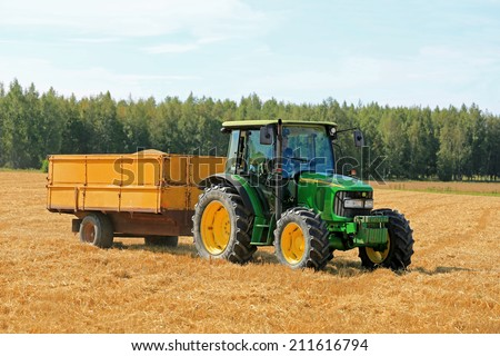 RAASEPORI, FINLAND - AUGUST 17, 2014: Unidentified farmer driving a John Deere 5820 agricultural tractor and trailer full of grain. John Deere 5820 was manufactured in 2003-2008 in Germany. - stock photo