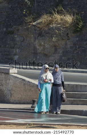 RABAT - JULY 23: Traditional clothed women crossing the road on July 23, 2014 in Rabat, Morocco. The city is located on the Atlantic Ocean at the mouth of the river Bou Regreg Rabat, Morocco. - stock photo