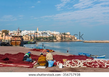 Rabat, Morocco - December 11, 2015: Fishermans fixing fishing net in Rabat fishing port, located in the river Bou Regreg at the mouth of the Atlantic Ocean. Kasbah of the Udayas in background. - stock photo