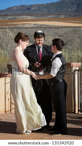 Rabbi blessing lesbian marriage ceremony in desert - stock photo