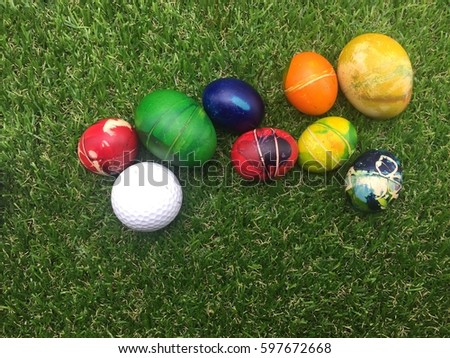 Rabbit and golf ball with Easter eggs on green grass