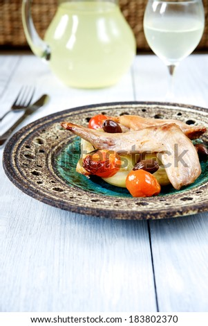 Rabbit baked with tomatoes, potatoes, rosemary and olives