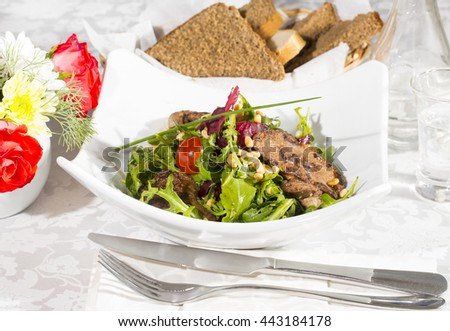 rabbit liver salad with arugula in a restaurant - stock photo