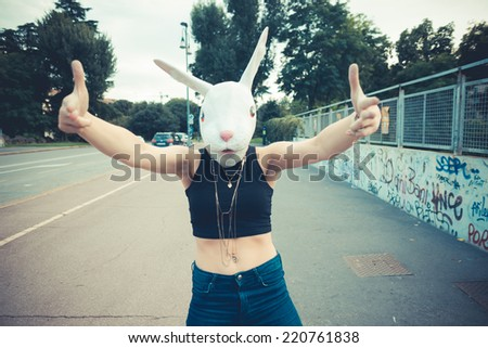rabbit mask woman absurd unreal in the city - stock photo
