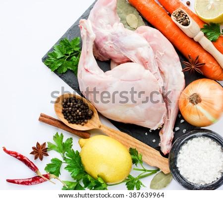 Rabbit meat and ingredients lemon onion carrot garlic seasoning spice herb on white background - stock photo
