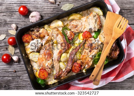 rabbit meat baked in sour cream with tomatoes, peppers, garlic, potatoes and spices,view from above, horizontal. rustic style