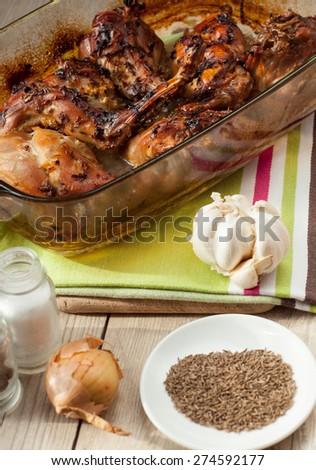 rabbit meat roaster with onion cumin and garlic on wooden vintage table