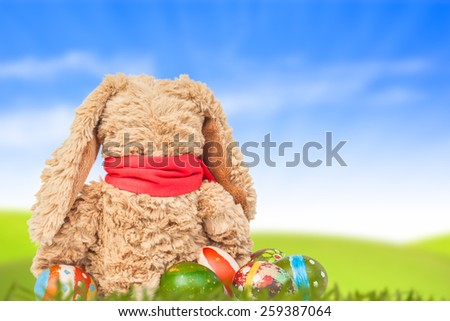 Rabbit, sit on green grass and group of colorful eggs are behind with blue sky background for happy easter festival - stock photo