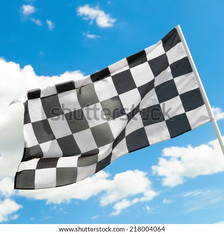 Race flag waving in the wind with white clouds on background - outdoors shoot - 1 to 1 ratio - stock photo