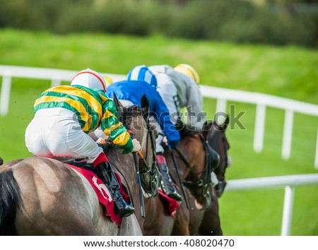 Race horses and jockeys racing down the track - stock photo