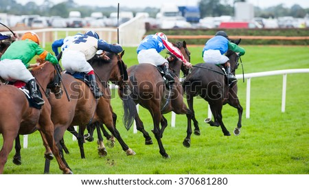 Race horses running towards the finish line - stock photo