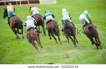 race horses taking a sharp turn on the race track - stock photo