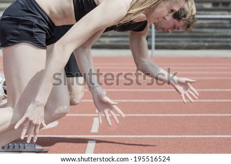 Race of male and female track and field athletes in a stadium - stock photo