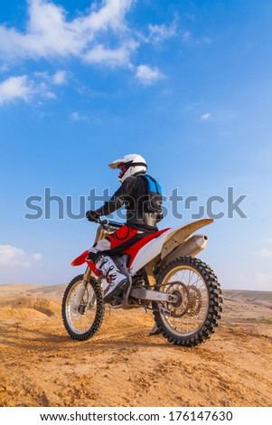 racer on a motorcycle in the desert summer day - stock photo