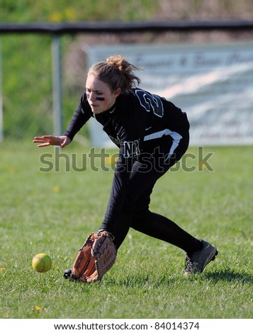 RACHEL, WV - APRIL 21: A North Marion HS (WV) softball player fields a grounder in the outfield prior to a game against Cameron April 21, 2011 in Rachel, WV. - stock photo