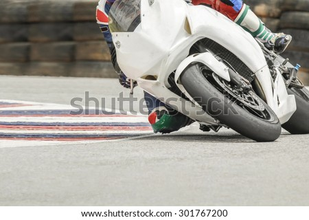 Racing bike rider leaning into a fast corner on track  - stock photo