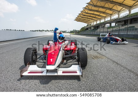 racing car driver celebrate victory sign in sepang f1 track
