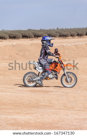 racing motorcycles for teenagers on desert area, summer day - stock photo