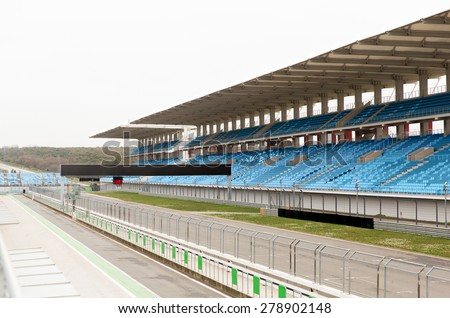 racing, motosports, extreme and motoring concept - empty speedway and bleachers on stadium - stock photo