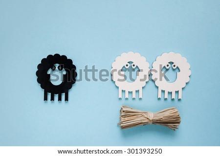 Racism. Cartoon lambs on cyan background - stock photo