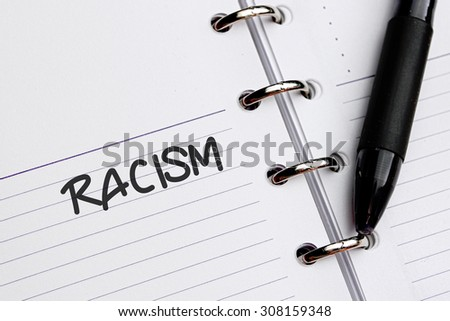 RACISM word written on notebook - stock photo