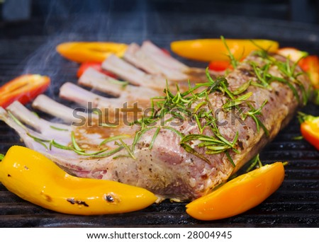 rack of lamb and bell peppers cooking on a grill - stock photo