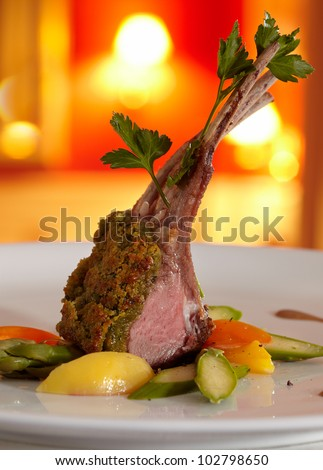 Rack of lamb in a herb crust, served with ratatouille and Port wine-sauce. Close-up. In the background a restaurant in red colours, blurred. - stock photo