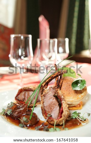 Rack of lamb with caramelized onions and homemade bun on restaurant table