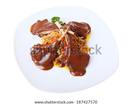 Rack of lamb with sauce and garnish of mushrooms and vegetables on white dish isolated on white background. Side view. - stock photo