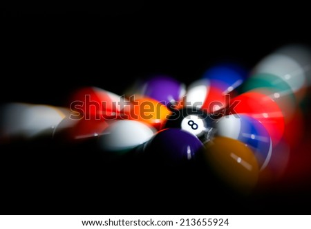 Rack of pool balls with 8 ball in center and radial blur applied to illustrate motion of a break shot. - stock photo