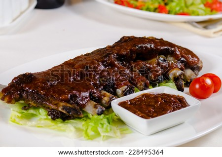 Rack of Saucy Barbecue Pork Ribs on White Plate Served in Restaurant