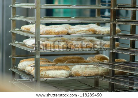 Rack trolley with baked bread in department of supermarket - stock photo